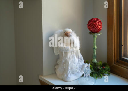 A Christmas decoration of an angel, candlestick and red ornament. USA - Stock Image