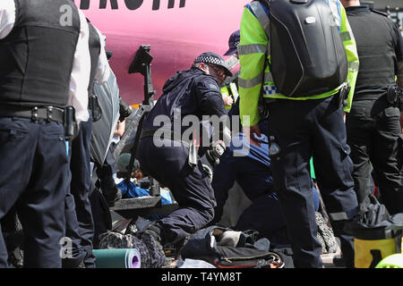 Police prepare to remove Extinction Rebellion demonstrators from the boat at Oxford Circus in London. - Stock Image