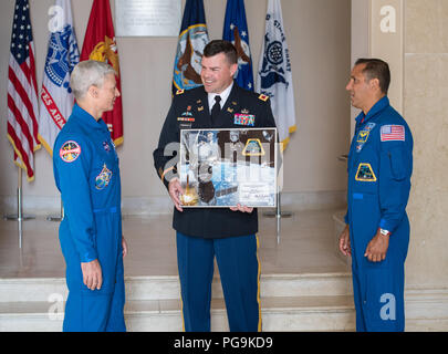 NASA astronauts Mark Vande Hei, left, and Joe Acaba, right, present Jerry Farnsworth, chief of staff at Arlington National Cemetery with a montage from Expedition 54, Friday, June 15, 2018 in Arlington, Va. - Stock Image