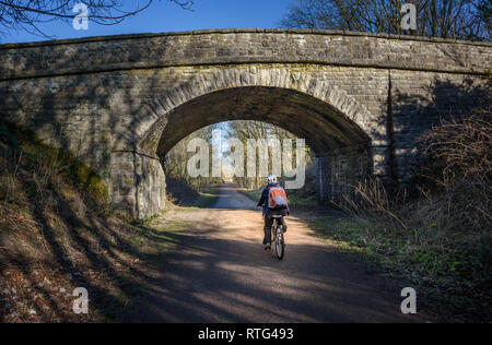 A cyclist passing under one of the railway viaducts on teh Monsal Trail, Derbyshire, Peak District, Uk. - Stock Image