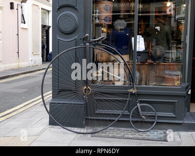 Old Penny Farthing Bicycle outside Thomas Farthing Gentleman's outfitters corner of Gilbert Place and Museum Street, London. - Stock Image