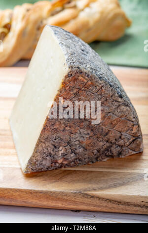 Italian cheese, piece of mature Tuscan Pecorino sheep cheese served with olive bread and tomatoes close up - Stock Image