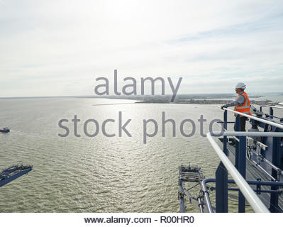 Dock worker looking at view from crane railing - Stock Image