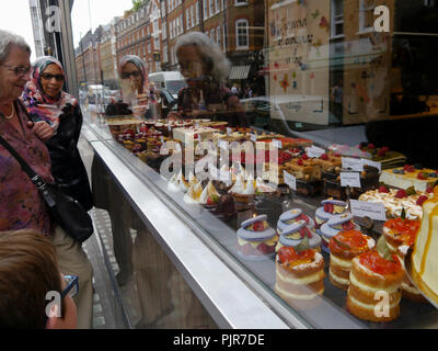 People look at cakes through a bakery shop window - Stock Image