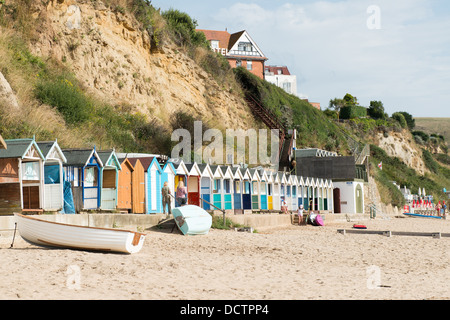 Brightly coloured wooden beach huts on the sandy beach at Swanage in Dorset with a cliff in the background. - Stock Image
