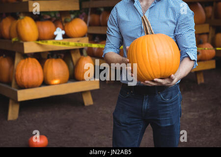 Man holding pumpkin at supermarket - Stock Image