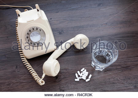 Old fashioned telephone with receiver off the hook and a glass of water with tablets - Stock Image