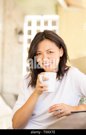Portrait of an Asian woman laughing and smiling. - Stock Image