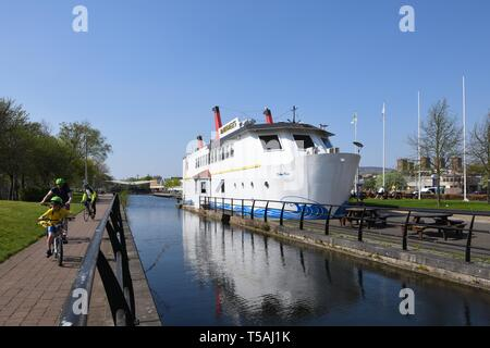 The Forth and Clyde canal in Clydebank with McMonagles fish and chip shop which resembles a moored ship. - Stock Image