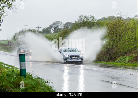 Skibbereen, West Cork, Ireland. 15th Apr, 2019. Much of Ireland is currently in the midst of a Status Orange Rainfall Warning, issued by Met Éireann. A car races through a spot flood on the N71 near Skibbereen. Credit: Andy Gibson/Alamy Live News - Stock Image