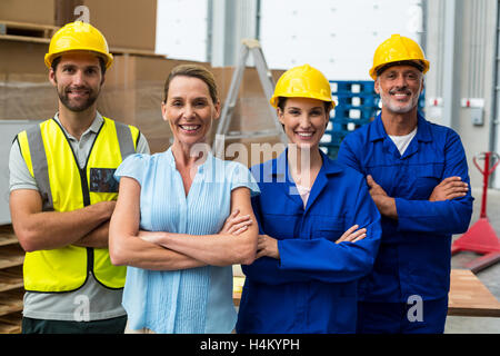 Portrait of warehouse manager and worker standing together with arms crossed - Stock Image