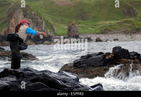 Salt water fly fisherman Dave Felce casting a fly fishing rod into the sea off the East coast of Scotland - Stock Image