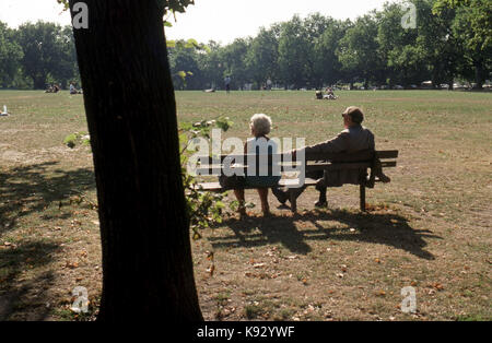 back view of elderly couple seated on park bench in the sunshine - Stock Image