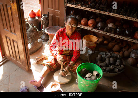 This elderly Nepali lady is one of the few potters left in  Bhaktapur, Nepal. - Stock Image