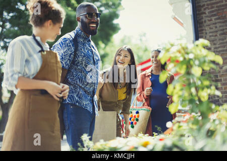 Female florist helping friends at sunny flower shop storefront - Stock Image