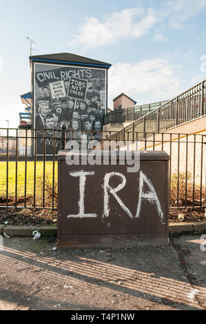 IRA grafittied on a street cabinet with a Republican mural in the background, Londonderry, Derry, Northern Ireland, UK, United Kingdom - Stock Image