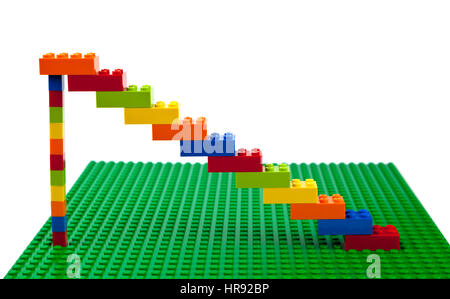 Colourful Lego brick construction of staircase or artwork  on a green Lego base plate. - Stock Image