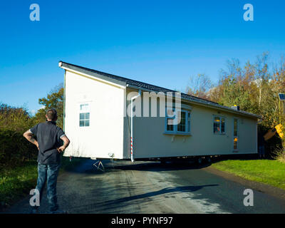 A prefabricated section of a static home building stuck in a narrow site entrance and being manoeuvered into place by a gang of men - Stock Image