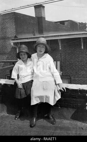 Two young girls pose  on the roof of their New York City apartment, ca. 1932. - Stock Image