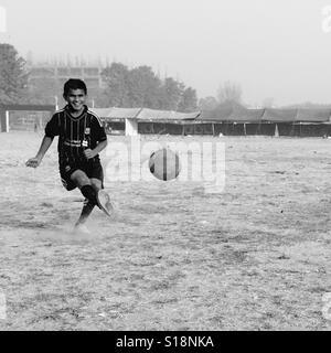 Boy kicking a football - Stock Image