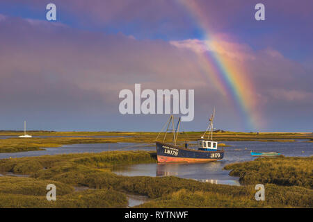 Fishing boat under a rainbow on a stormy day. - Stock Image