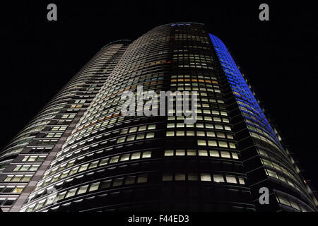 Modern office building at night with blue and white lights - Stock Image
