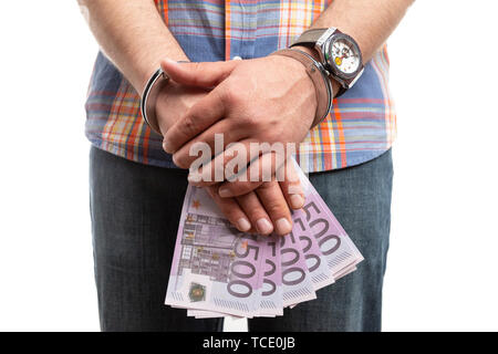 Closeup of man with handcuffed hands holding cash money as corruption  and bribe concept isolated on white - Stock Image