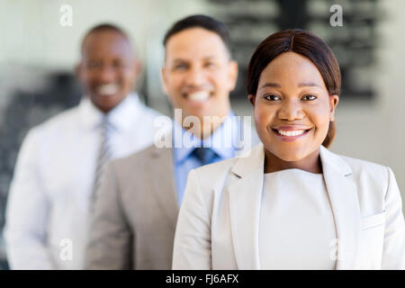 smiling African businesswoman with colleagues standing in a row - Stock Image