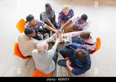 Men joining hands in circle in prayer group - Stock Image