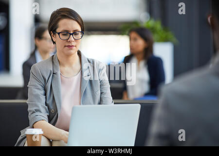 Serious concentrated attractive lady in glasses sitting on sofa and analyzing sales report on laptop while working remotely - Stock Image