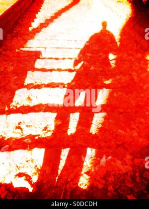 Shadow of man walking down stairs - Stock Image