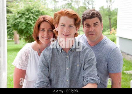 A handsome ginger red head boy with his proud smiling parents - Stock Image