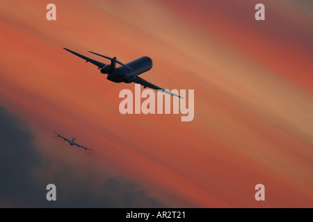 Two aeroplanes climbing out after take off against dramatic red sky. - Stock Image