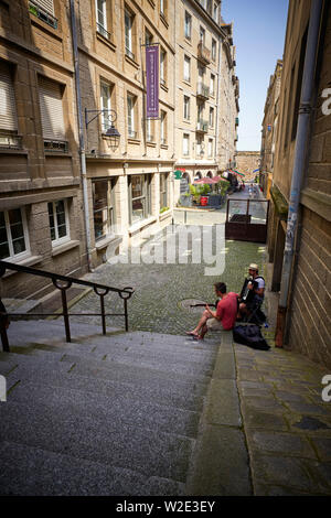 Street musicians practicing in a quiet street in St Malo, Brittany, France - Stock Image