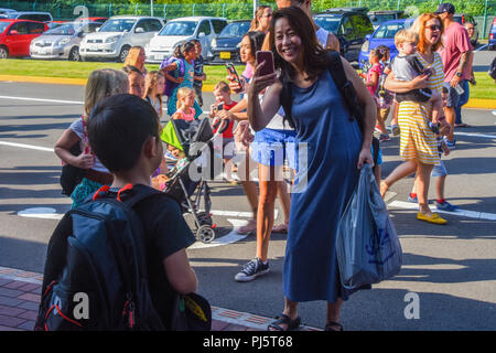 ZUSHI, Japan (Aug. 27, 2018) A parent takes a photo of her child on the first day of school at U.S. Fleet Activities (FLEACT) Yokosuka's Ikego Elementary School. FLEACT provides, maintains, and operates base facilities and services in support of 7th Fleet's forward-deployed naval forces, 71 tenant commands, and 27,000 military and civilian personnel. (U.S. Navy photo by Maria Dumanlang/Released by FLEACT Yokosuka Public Affairs Office) - Stock Image