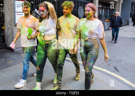 London, UK. 20th March, 2019. Students from St George's University of London Hindu Society leave King's College London after celebrating Holi. Holi is an ancient Hindu spring festival, or festival of colours, signifying the arrival of spring, the arrival of the spring harvest season, the end of winter and the blossoming of love. Credit: Mark Kerrison/Alamy Live News - Stock Image