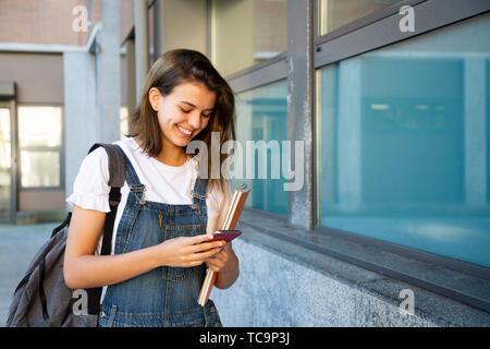 Happy student girl using smart phone at the school corridor - Stock Image