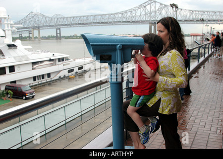 Mother helping son view the sites through binoculars, New Orleans, LA, USA - Stock Image
