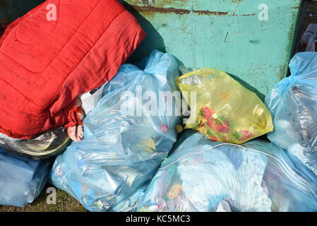 Piles of rubbish in plastic bags stacked against a green metal refuse bin waiting recycling or collection - Stock Image