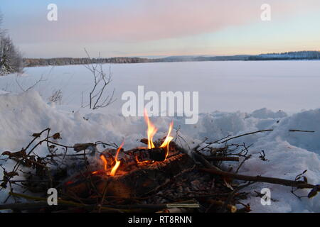 A fire is burning in the snow at the shore of an ice-covered lake as the sun is setting on a cold winter day. - Stock Image