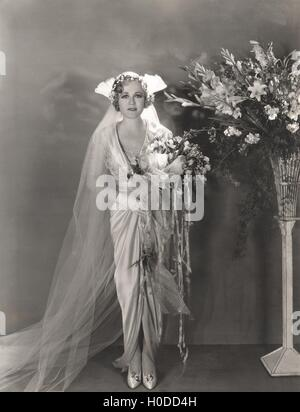 Bride standing next to tall vase of flowers - Stock Image