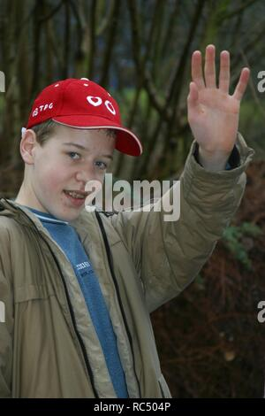 Teenage boy waving with his left hand, outside, and smile, braces - Stock Image
