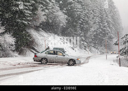Car without snow chains spins out of control blocking other cars during snowstorm on the Tombstone Pass in Oregon - Stock Image