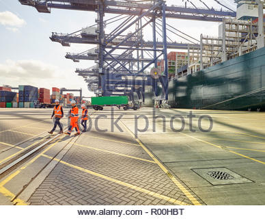 Dock team workers and supervisor walking away from cargo ship and containers at port - Stock Image