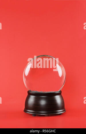 Blank snow globe with wooden base against a red background with free space for text. - Stock Image