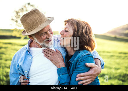 Happy senior couple outside in spring nature, hugging. - Stock Image