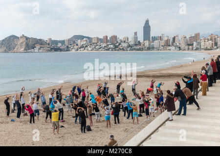 Seniors keeping fit on the beach in Benidorm, Spain. Men women oap's, elderly fitness class spectators watching - Stock Image
