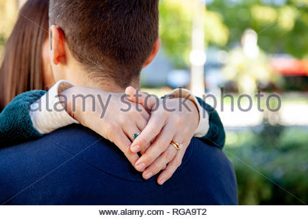 Hands of a woman hugging her boyfriend - Stock Image