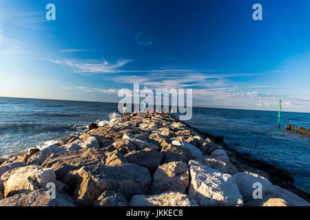 Group of fishermen fishing on the stones - shore of Adriatic Sea. Jesolo, Italy. - Stock Image