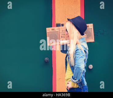 A blond hipster girl with glasses is listening to a vintage gold boombox radio with a speaker for a music entertainment - Stock Image